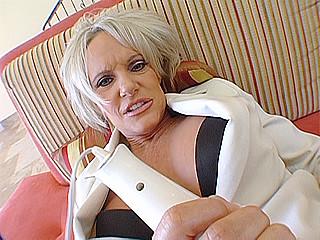 Allongée sur un canapé avec un gros vibro posé sur son clito une femme mûre se fait...